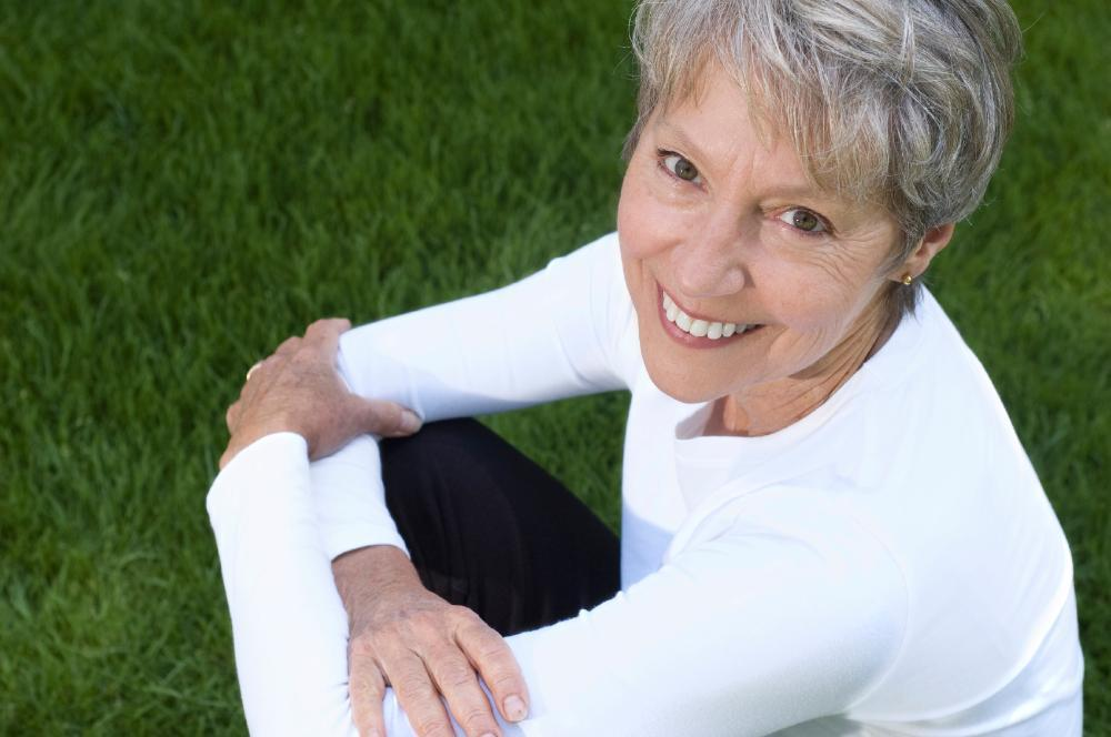 older woman sitting in a green park smiling I dental implants casuarina