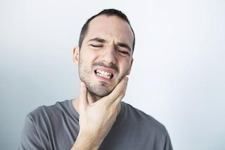 man holds his hand to his jaw | casuarina emergency dentist