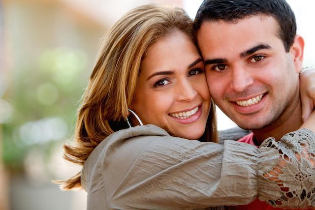 woman with veneers smiling next to man