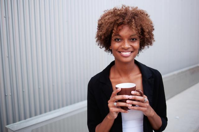 a woman smiles with coffee | dentist northern suburbs darwin