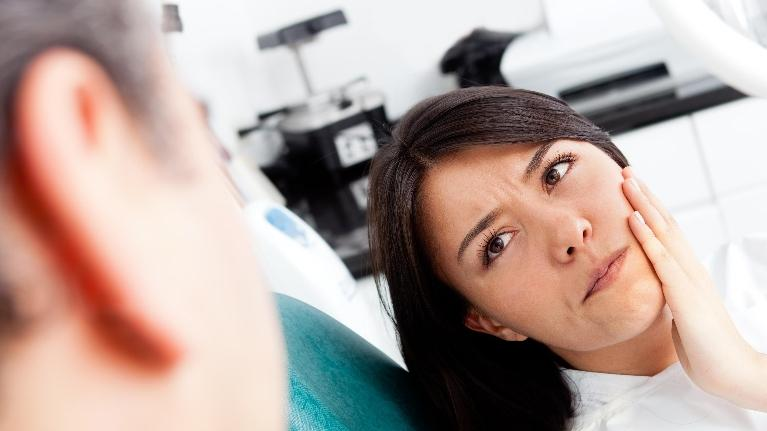 a woman holding her hand to her mouth, looking up at the dentist | Emergency Dentist Darwin NT