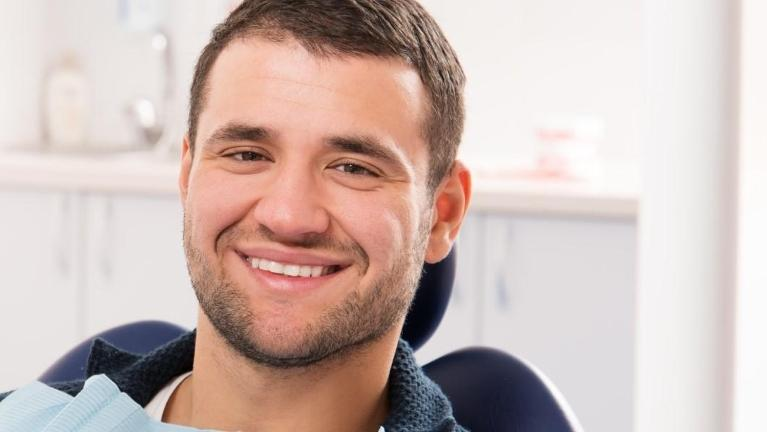 Man sitting in dentist chair smiling