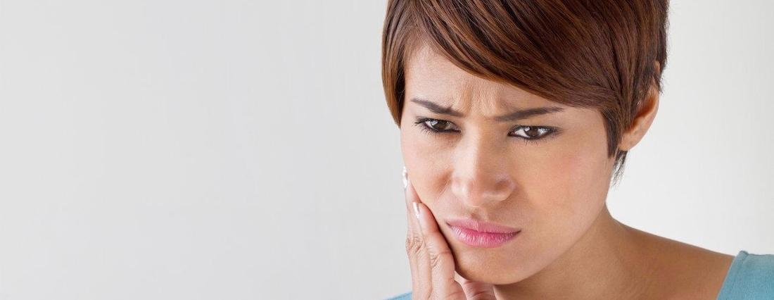 a woman holds her hand to her mouth | emergency dentist casuarina nt