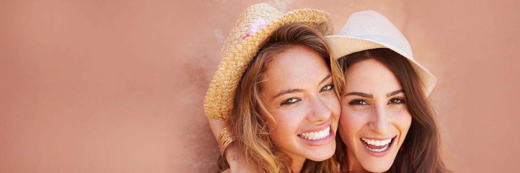 Two women in hats smiling
